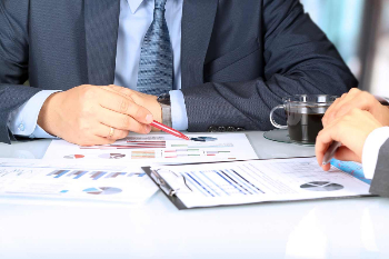 Man in business suit pointing at a graph with a pen. Across from him is another business person with their hands laying on work papers.