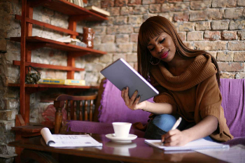Woman sitting on a couch smiling writing on a note pad on a table with a cup of coffee and holding a book.